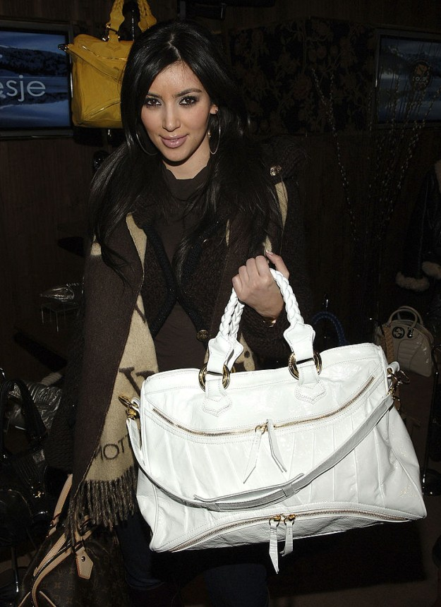 Carry a white handbag that is bigger than her actual self.