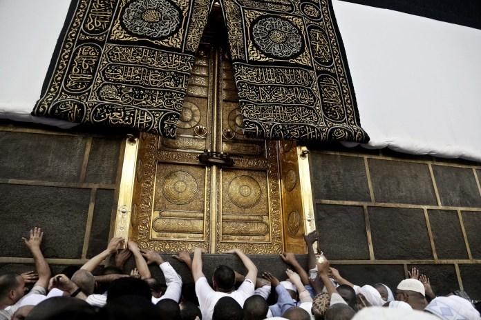 Touching the golden door of the Kaaba