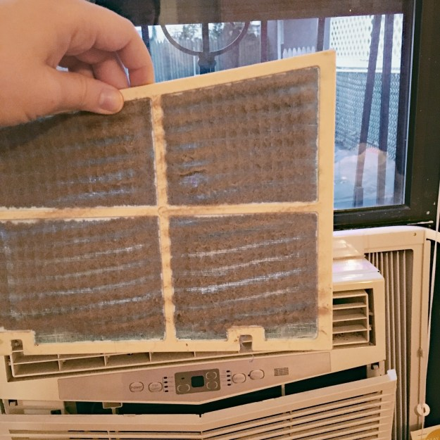 Rinse off all the dust on your window AC's small filter.