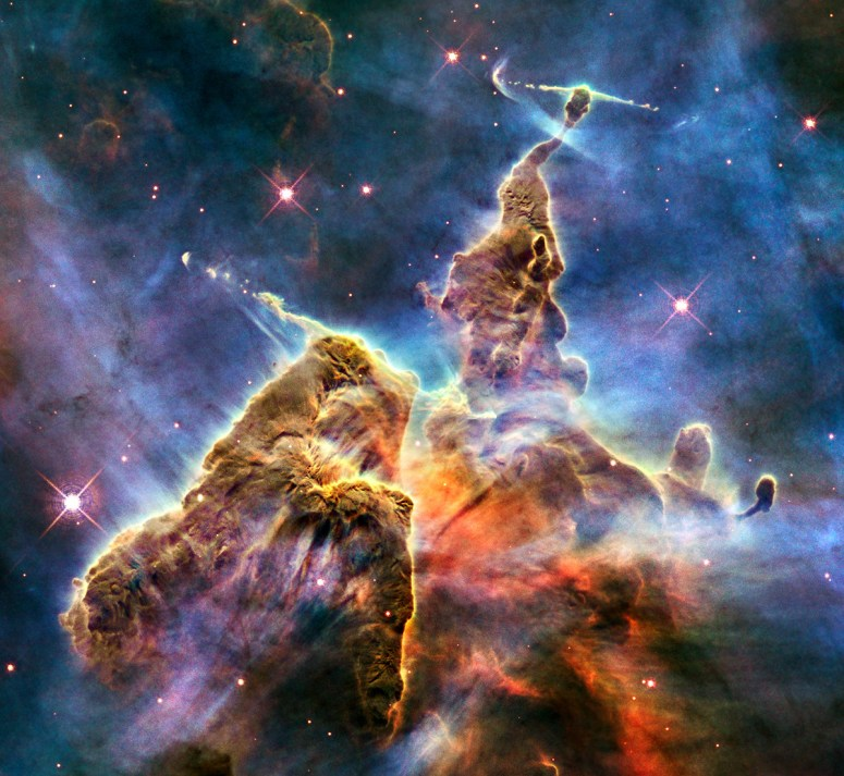The image captures the top of a pillar, which is three light-years tall, that is being eaten away by the brilliant light from nearby bright stars. The pillar, made of gas and dust, is also being pushed apart from within, as infant stars buried inside it fire off jets of gas that can be seen streaming from towering peaks.