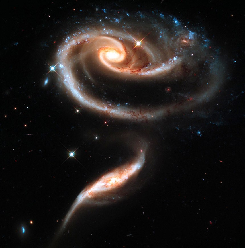The larger of the spiral galaxies, known as UGC 1810, has a disk that is distorted into a roselike shape by the gravitational tidal pull of the companion galaxy below it, known as UGC 1813. This image is a composite of Hubble Wide Field Camera 3 data taken on Dec. 17, 2010, with three separate filters that allow a broad range of wavelengths covering the ultraviolet, blue, and red portions of the spectrum.