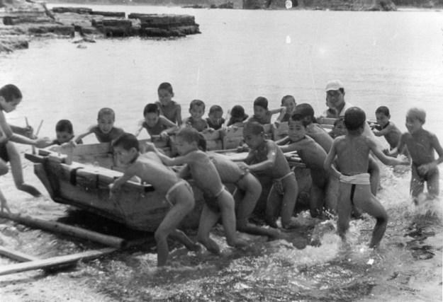 1945年10月。ミニチュアの揚陸艦で遊ぶ子どもたち。