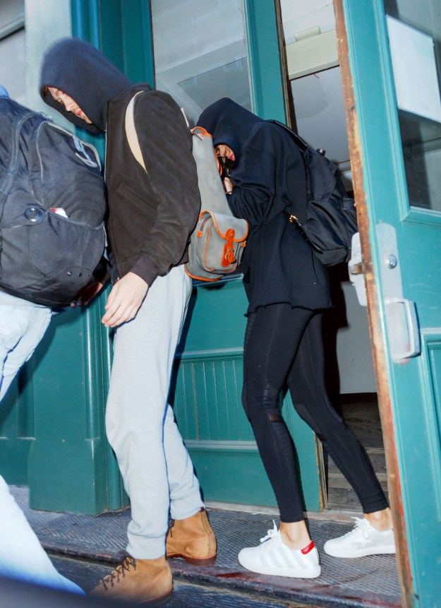 This is a photo taken of Taylor Swift and her ~rumoreddd~ new boyfriend Joe Something, leaving Taylor's Tribeca apartment. Notice how she is trying to hide from the cameras...