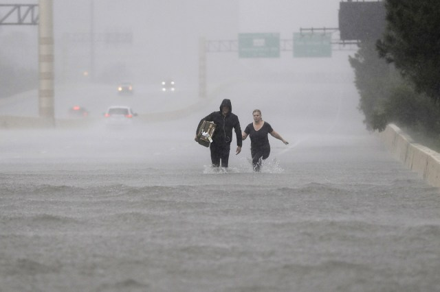 Dos personas caminan por una sección de la Interestatal 610 inundada a causa de la tormenta tropical Harvey, 27 de agosto de 2017, en Houston.