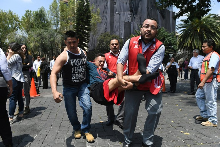 An injured man is carried away by rescuers in Mexico City.