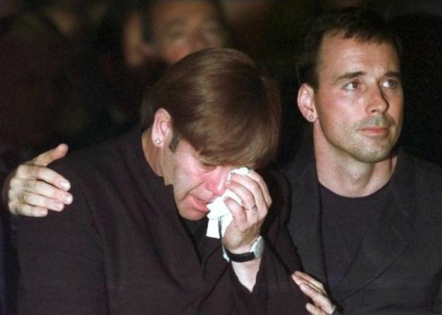 David Furnish comforted Sir Elton John during the ceremony.
