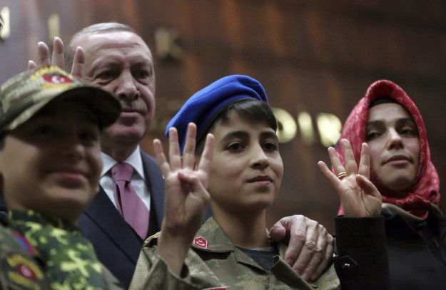 """And here they are holding up four fingers, symbolizing Erdogan's current mantra of """"one nation, one state, one homeland, one flag."""""""