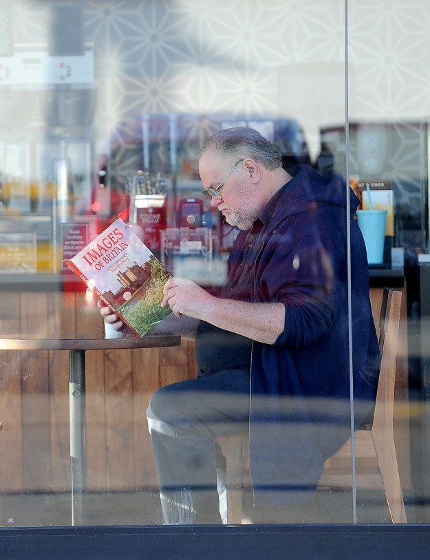 "He is just casually sitting in a Starbucks reading ""Images of Britain: A Pictorial Journey Through History."""