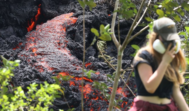 Lava flows at a new fissure on May 12 as a local resident walks nearby after taking photos.