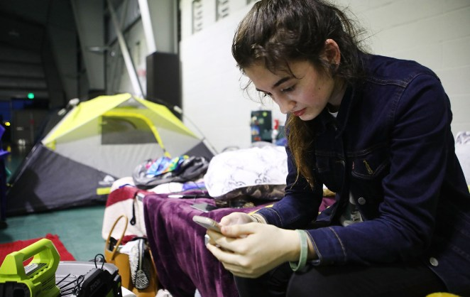 Evacuee Taylor Burns checks her phone in the emergency shelter at the Pahoa Community Center on May 5.