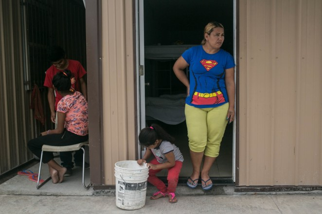 Claudia with her daughter, 6, looks out from her shared room at a shelter in Reynosa