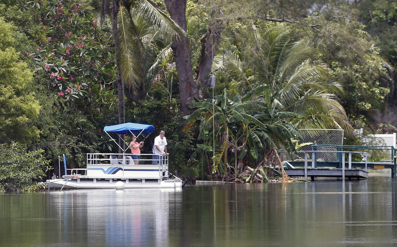 A couple looks out from a pontoon boat on one of the lakes at Silver Lakes Rotary Nature Park on June 8.