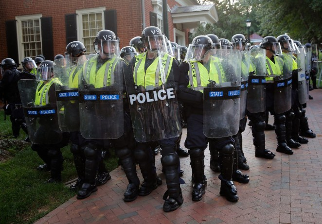 Members of the Virginia State Police stand guard in riot gear on the campus of the University of Virginia.