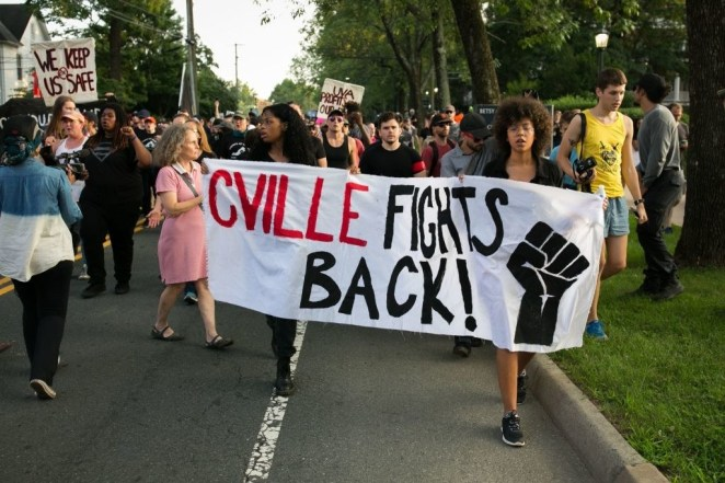 Demonstrators march down Rugby Avenue near the University of Virginia campus.