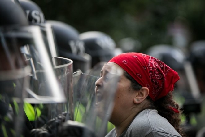 An activist confronts Virginia State Troopers in riot gear.