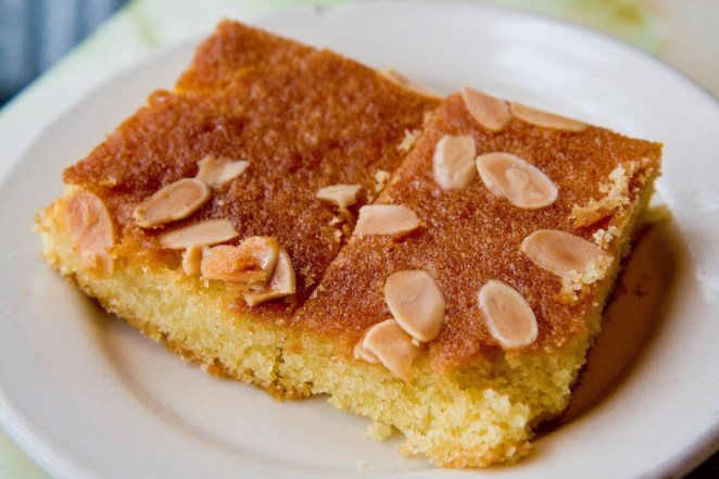 """A much loved traditional dessert in Libya called basbousa. It's a semolina based cake drenched in a sugar honey syrup topped with nuts (usually almonds or pistachios). People came up with many variations of the dessert but the classic one is heavenly!"" —ghadah3"