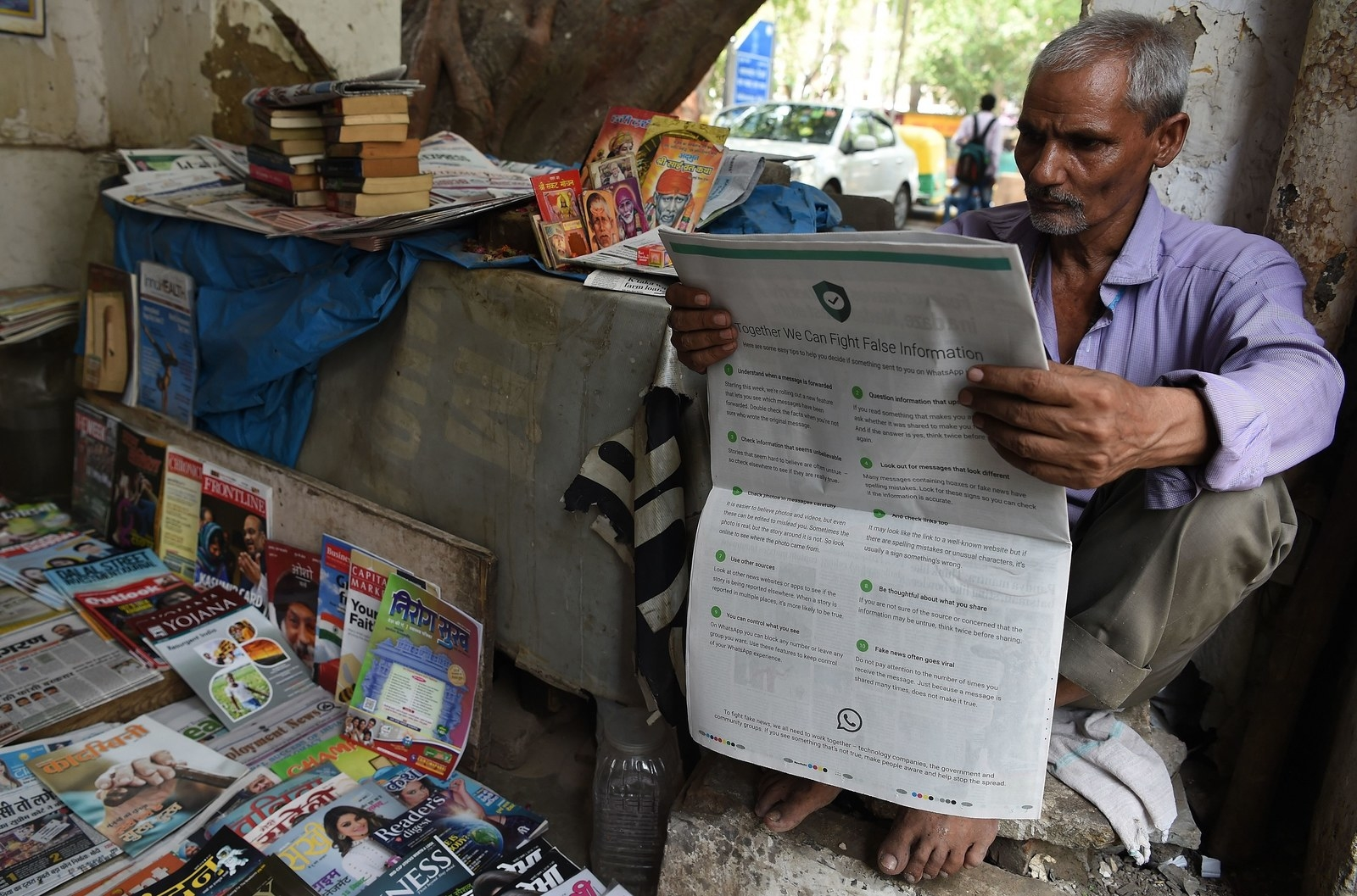 An Indian newspaper vendor reading a newspaper with a full backpage advertisement from WhatsApp intended to counter fake information, in New Delhi, on July 10, 2018.