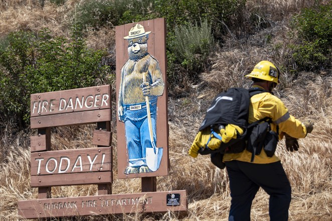 A firefighter passes by a Smokey Bear fire danger sign during a brush fire in Burbank, California, on May 25, 2018.