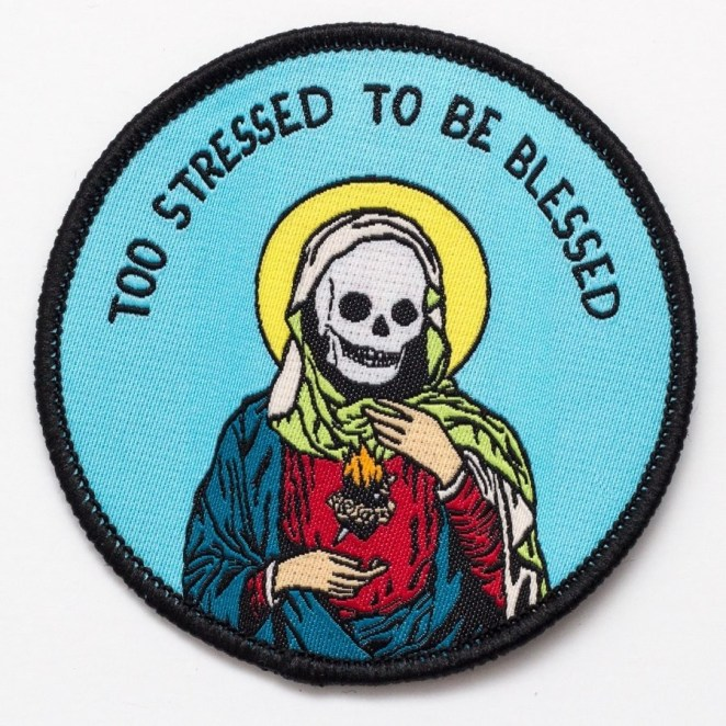 """a circle patch with a scull in the middle and the words """"too stressed to be blessed"""" on it"""