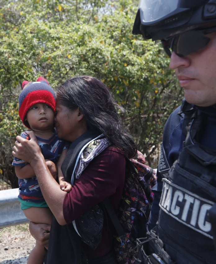 A Central American migrant woman and her son walk with a Mexican Federal Police agent as they are taken into custody.