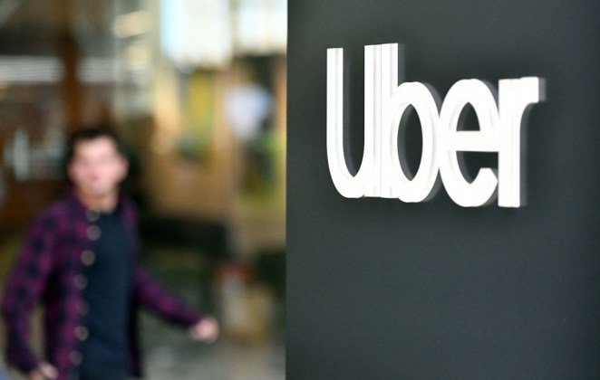 An Uber logo is seen on a sign outside the company's headquarters location as people protest nearby in San Francisco, California on May 8, 2019.