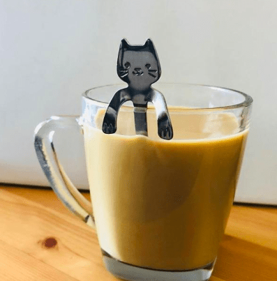 reviewer pic of a cat-shaped spoon with little arms that rest on the edge of a coffee mug