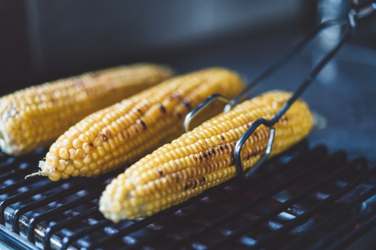 Three ears of corn on the cob on the grill.