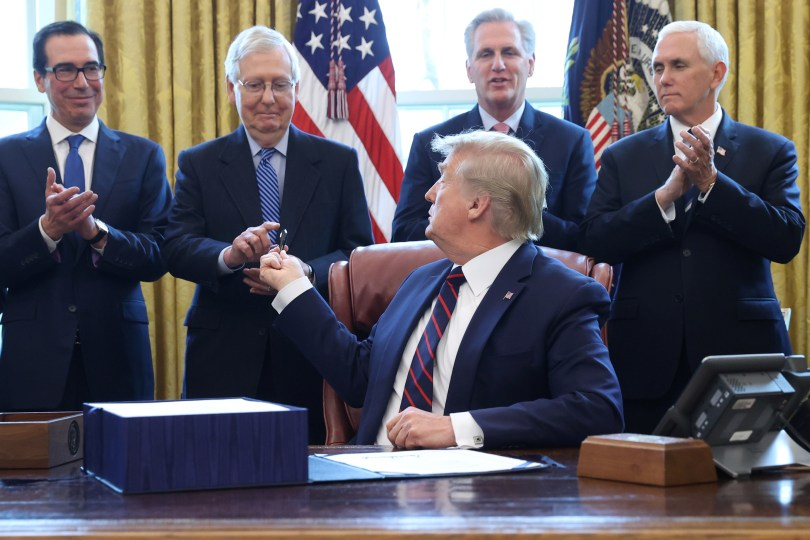 President Trump sits at the Resolute Desk in the Oval Office with Steven Mnuchin, Mitch McConnell, Kevin McCarthy, and Mike Pence applauding behind him