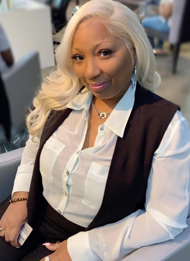 Margaret McNair is shown with long white hair and wearing a collared shirt and a vest as she smiles up at the camera.