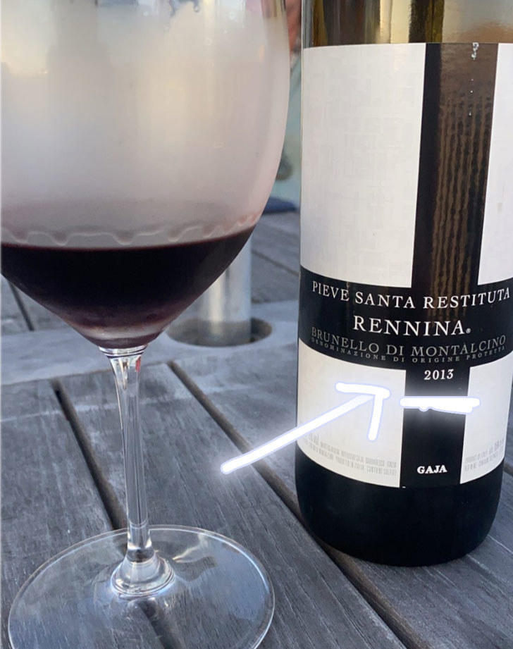 A bottle and glass of wine with an arrow pointing to the year on the label