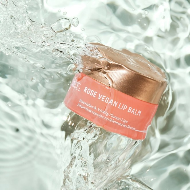 Biossance's Squalane + Rose lip balm immersed in water