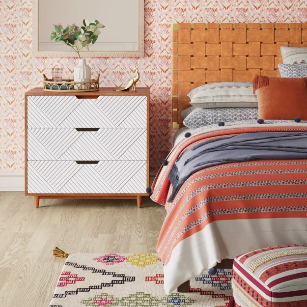 The dresser with geometrically textured white drawers next to a bed