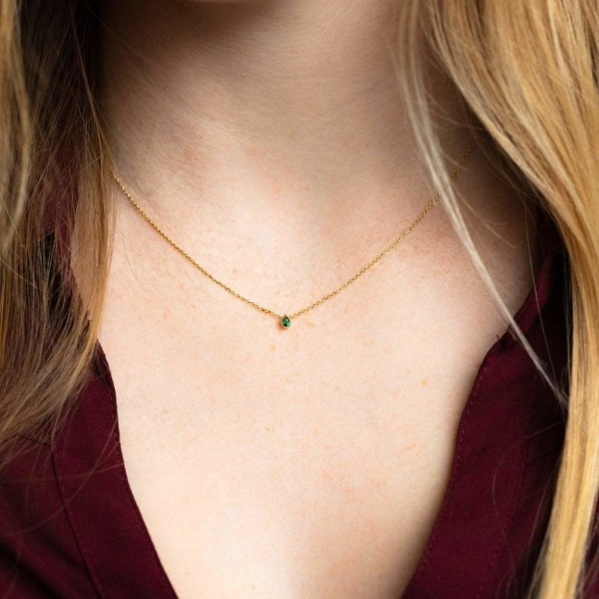 a model wearing the tiny emerald teardrop charm necklace