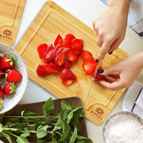 Model uses the bamboo cutting board to cut strawberries