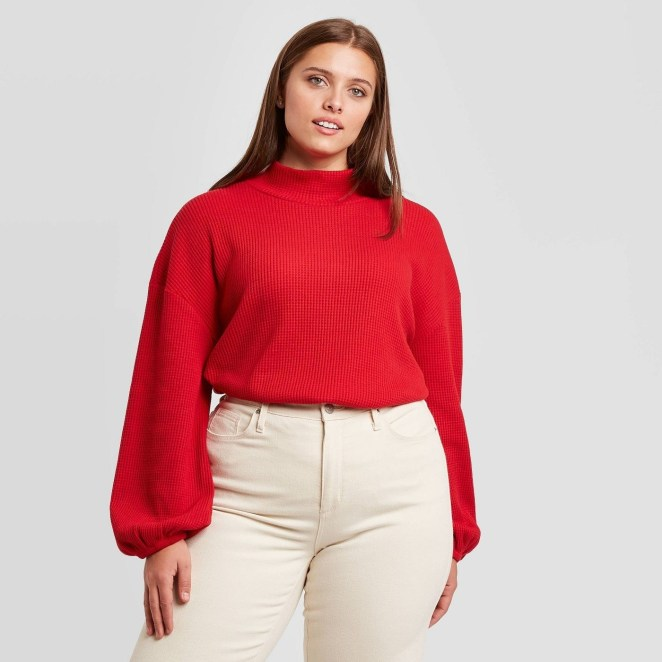 A model wearing a red mock turtleneck sweater with puffy sleeves