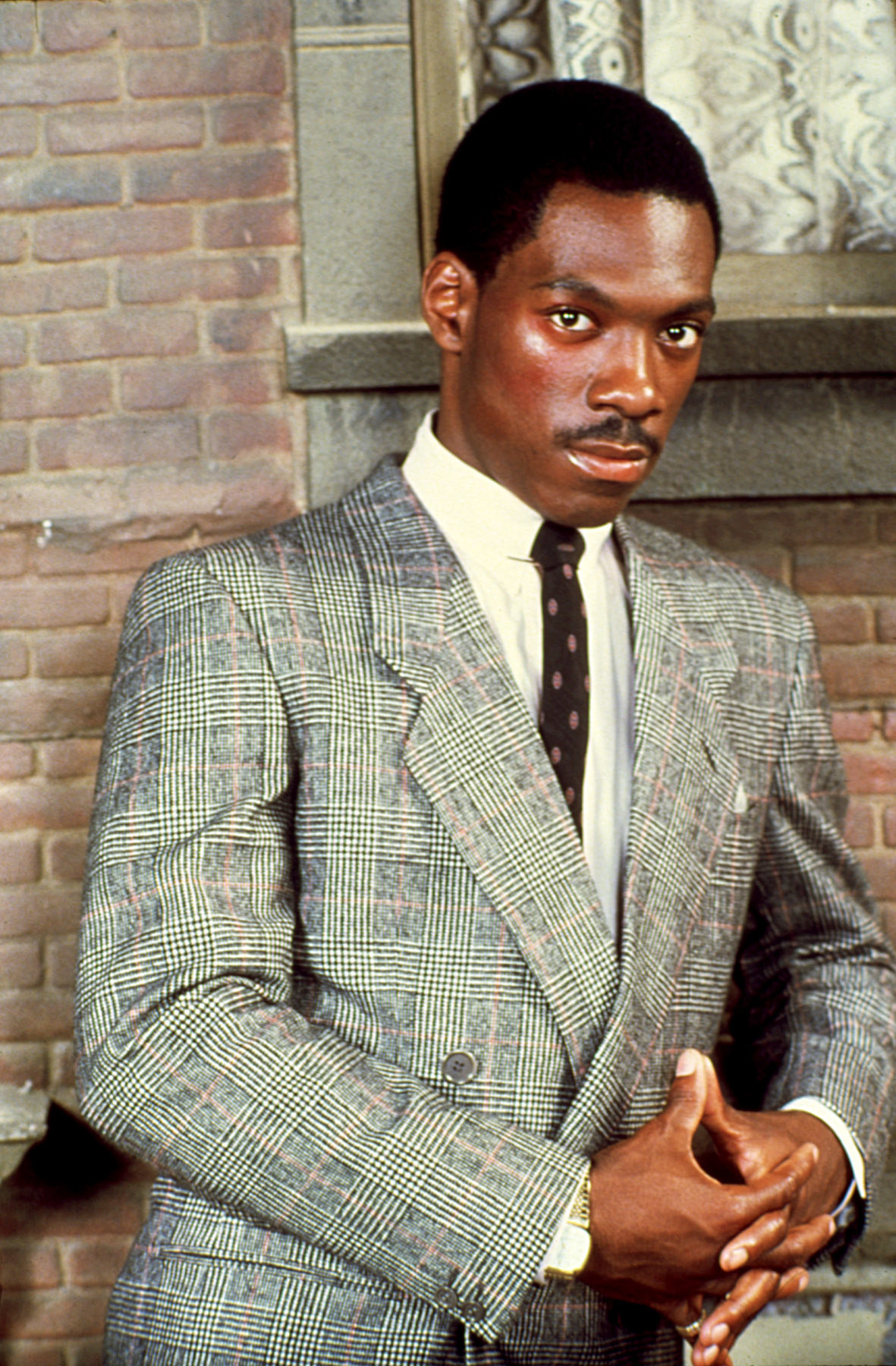 Eddie Murphy in a suit, leaning against a brick wall