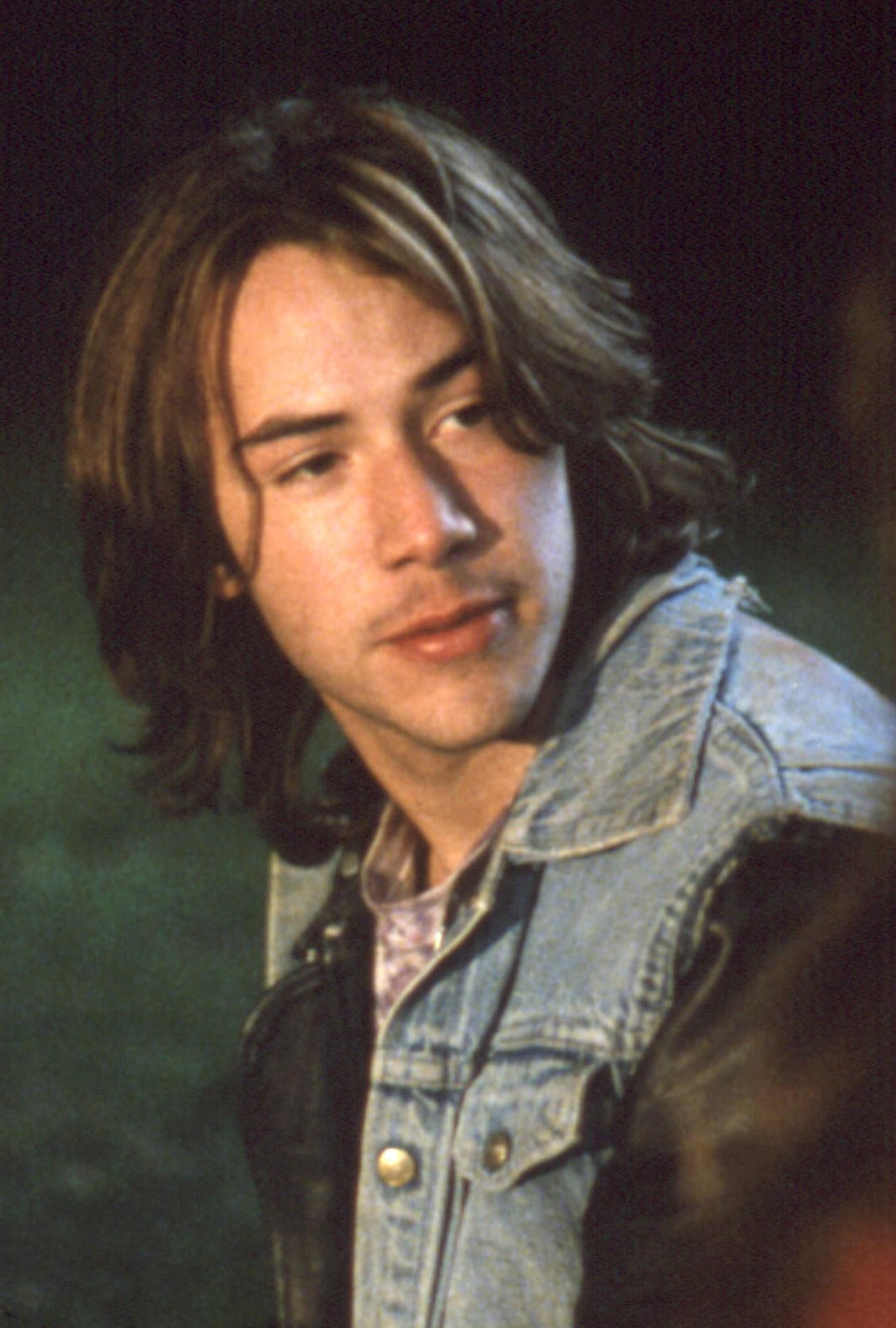 Keanu Reeves wearing a jean/leather jacket, sitting in a field