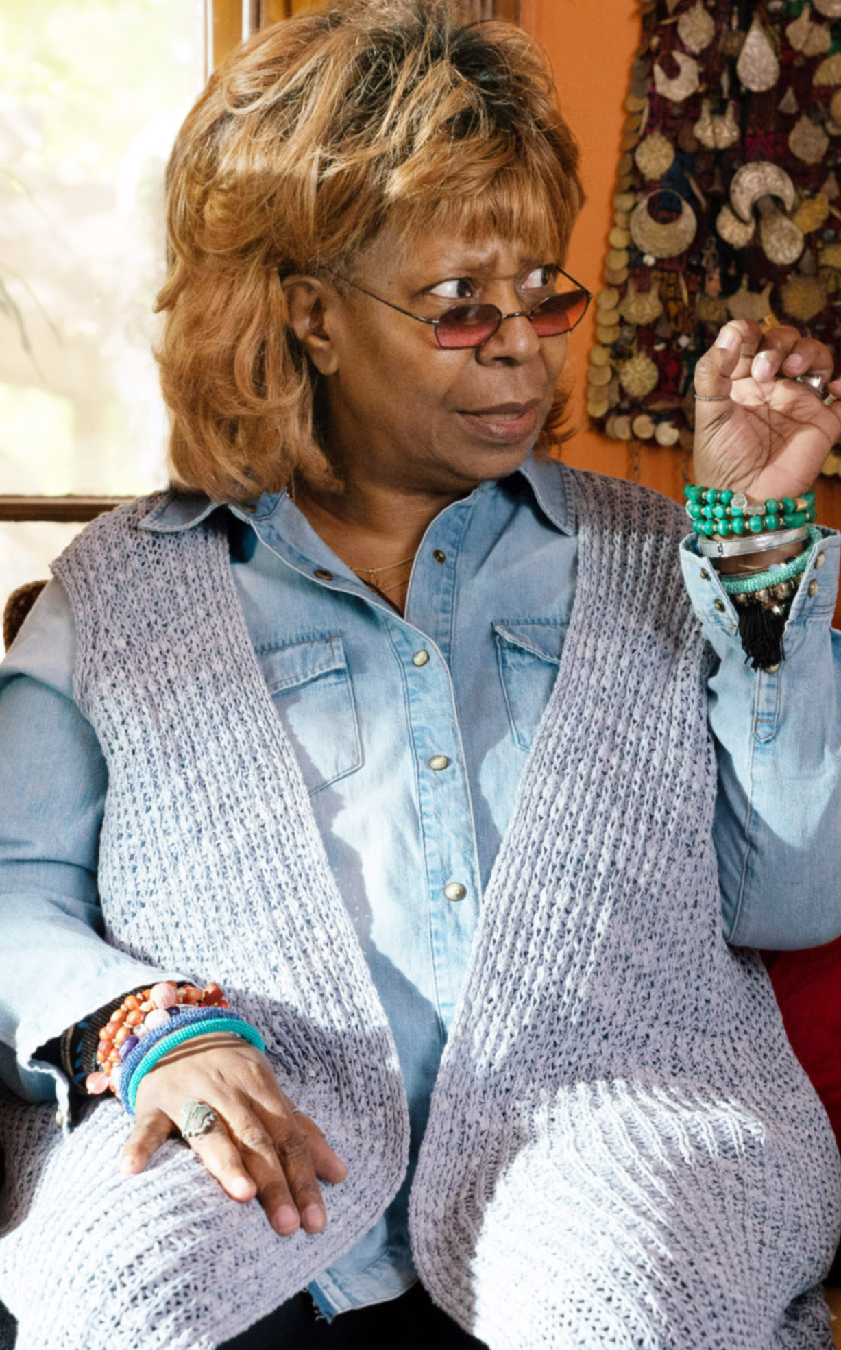 Whoopi Goldberg wearing colorful jewelry, clothes, and glasses while making a puzzled face