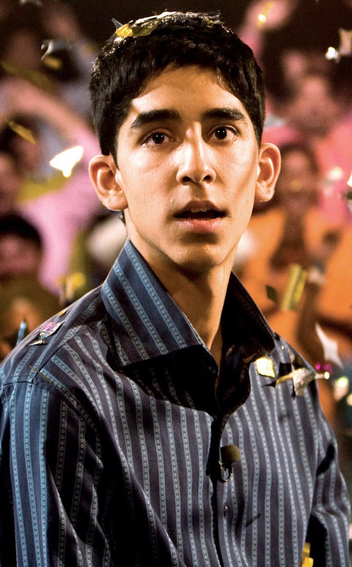 Dev Patel making a surprised face while confetti falls all around him