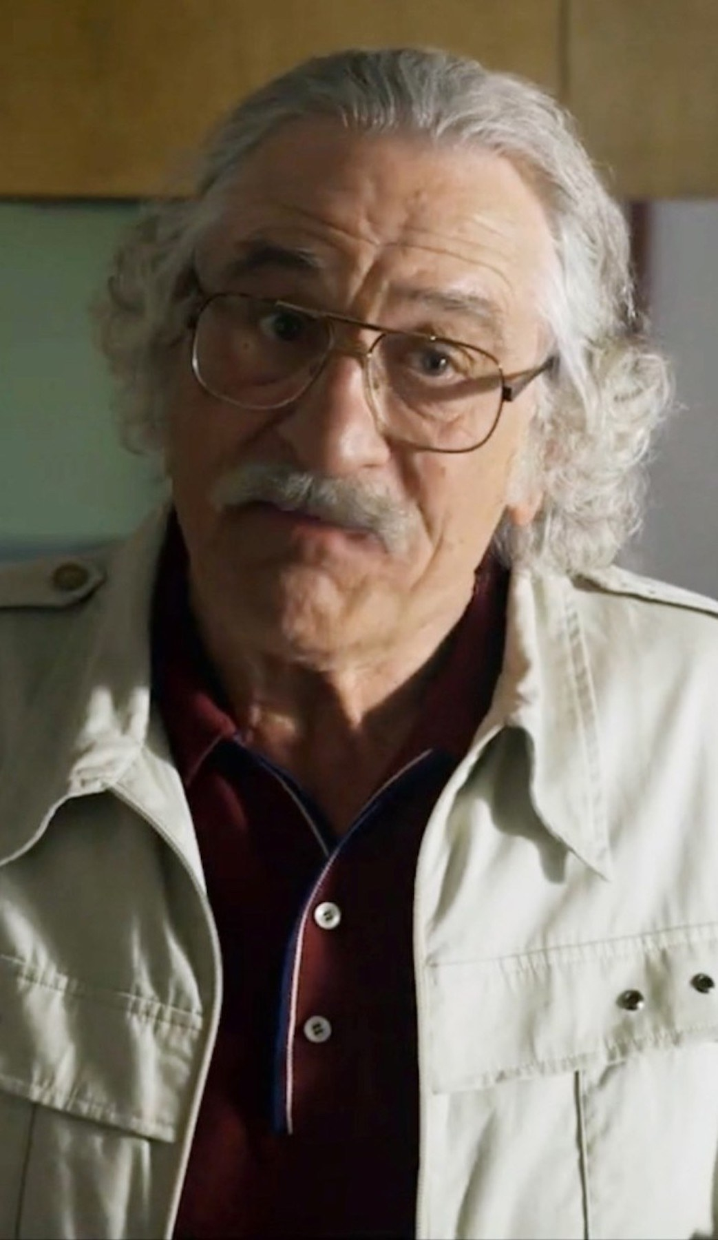 Robert De Niro with long grey hair, a grey beard, and over-sized glasses