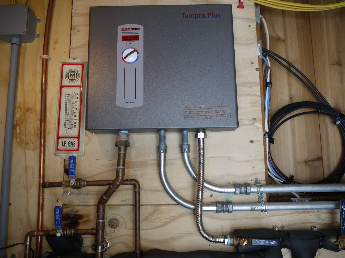 hight resolution of tankless water heater mounted to utility room wall