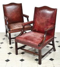 A pair of mahogany framed maroon studded leather ...