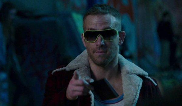 Deadpool Ryan Reynolds portant des lunettes de soleil la nuit, pointant avec désinvolture vers la caméra
