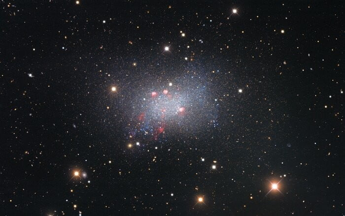 Sextans B is an irregular dwarf galaxy, meaning that it is irregularly shaped and smaller than our galaxy, the Milky Way. It lies around 4.5 million light-years from Earth and is located in the constellation Sextans in the southern sky. Captured with the Nicholas U. Mayall 4-meter Telescope, this image of Sextans B features red-colored star-forming regions near the galaxy's center. Surrounding the galaxy are several bright stars that are located much closer to us in our galaxy, identified by the crisscross patterns created by light interacting with the structure of the telescope, as well as numerous fuzzy-looking background galaxies that appear small because they are much farther away than Sextans B.