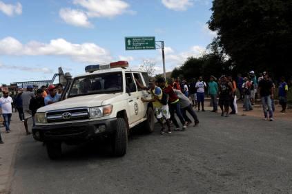 Venezuelanos socorrem feridos por ação da Guarda Nacional Bolivariana para ambulância que transportou as vítimas até hospitais no Brasil