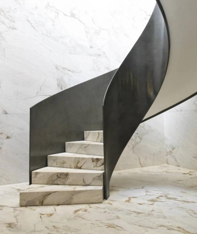 Escada escultural de mármore nas suítes dúplex