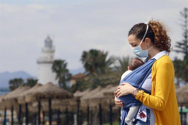 Archivo - Una mujer protegida con una mascarilla da un paseo con su bebé.