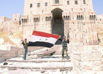 Soldados del gobierno sirio ondean la bandera nacional en Alepo