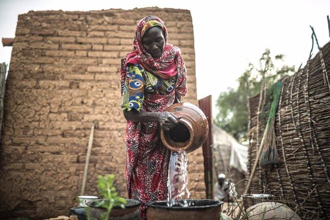 Akkoe Moussa, echando agua potable en un cántaro.