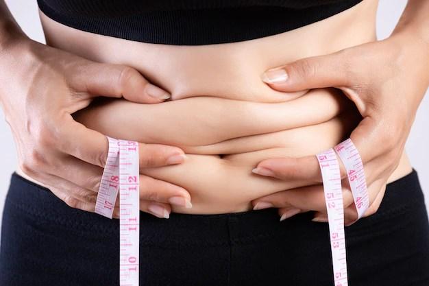 mao-de-mulher-gorda-segurando-a-gordura-da-barriga-excessiva-com-fita-metrica_53476-4091 Perder barriga rápido é possível?